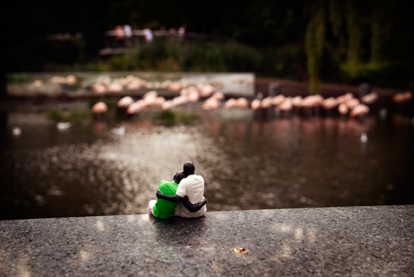 3D-printed refugees, (father-son pair from Rwanda) sit on a wall in Amsterdam.