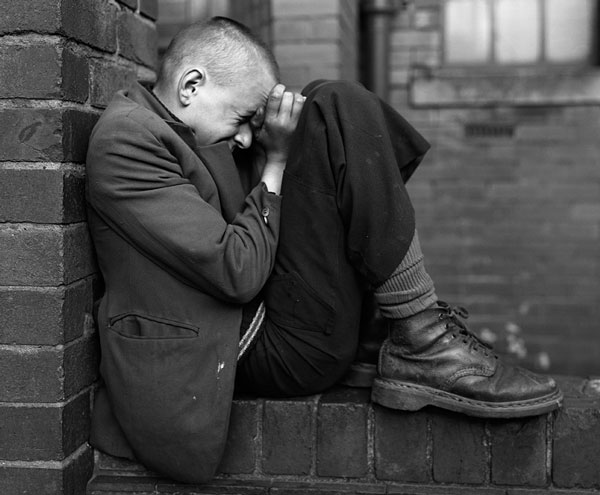 "Chris Killip, From the series ""In Flagrante Two,""Youth on wall, Jarrow, Tyneside, 1976, © Chris Killip, courtesy Yossi Milo Gallery, New York"