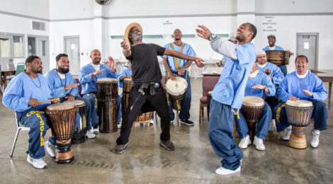 Peter Merts, Instructor Wilfred Mark of Dance Kaiso, in black, during drum and dance class at Salinas Valley State Prison, 2015, archival pigment print, 16 x 20 inches.
